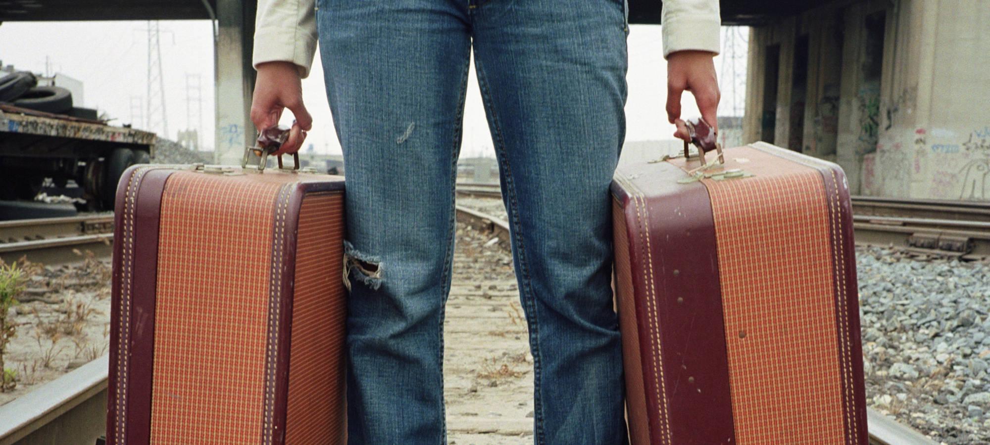Frau mit Koffer am Bahngleis