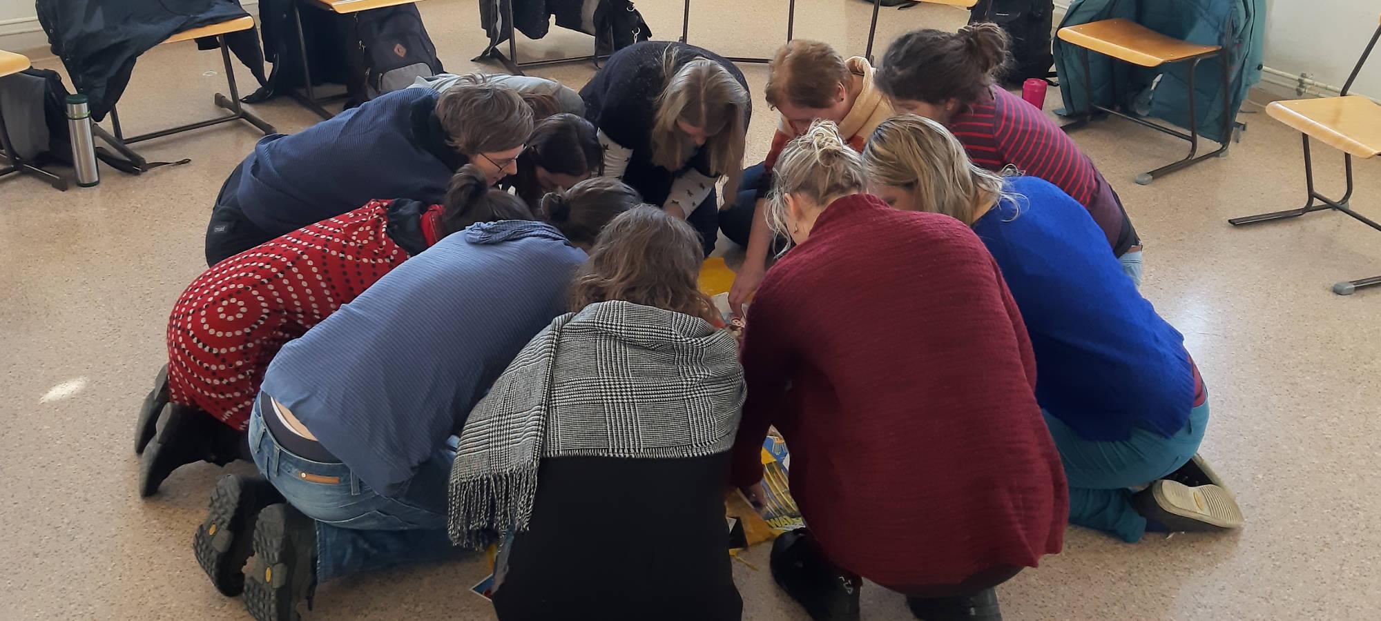 Menschen sitzen am Boden im Kreis in Rückenansicht