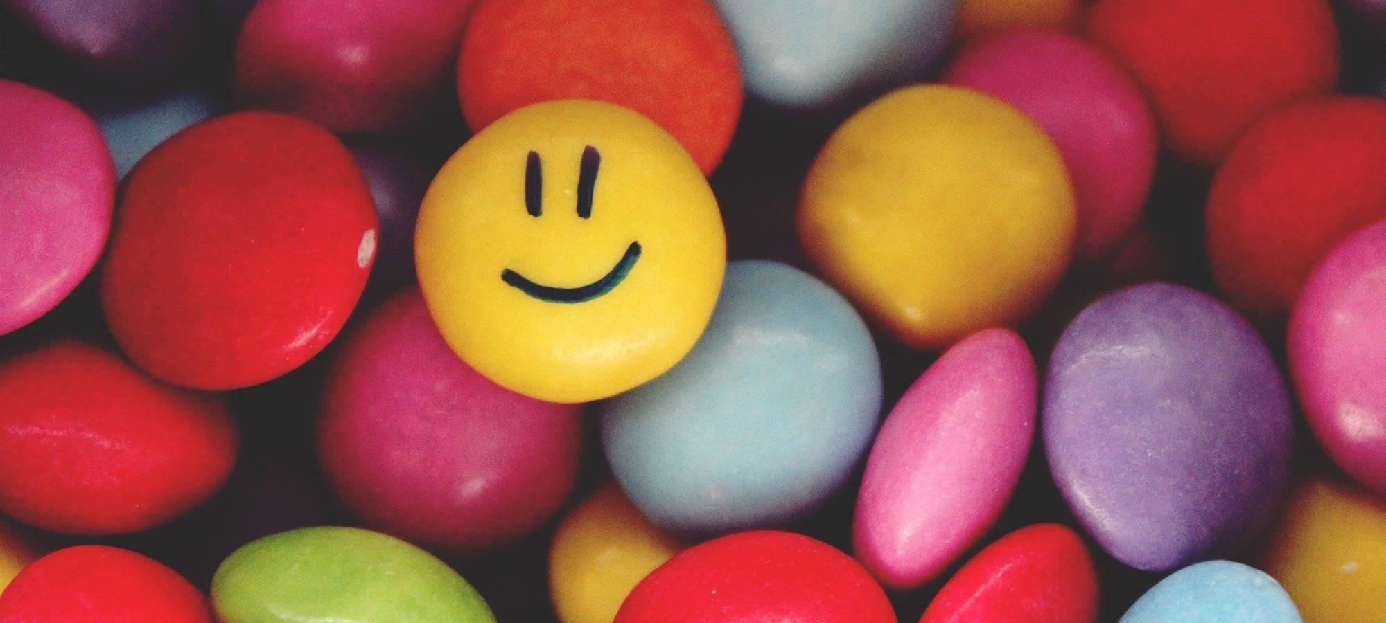 viele bunte smarties, eines davon mit smiley © pixabay