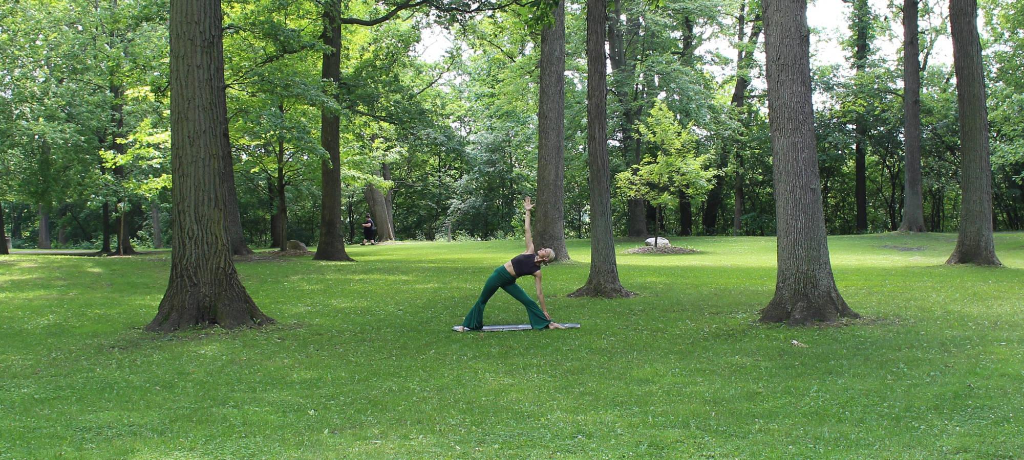 Park mit Bäumen und grüner Wiese, dazwischen eine Frau die Yoga macht, © unsplash